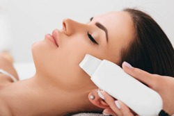 Beautiful woman receiving ultrasonic facial exfoliation at spa. Procedure clearing clogged pores, ultrasonic treatment for skin rejuvenation