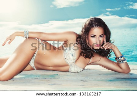 beautiful woman relax by pool sky with sun and clouds in background