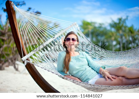 Beautiful woman relaxing at hammock on tropical beach