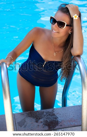 Beautiful woman relaxing at the luxury poolside, tanning. Girl at travel spa resort pool. Summer luxury vacation.