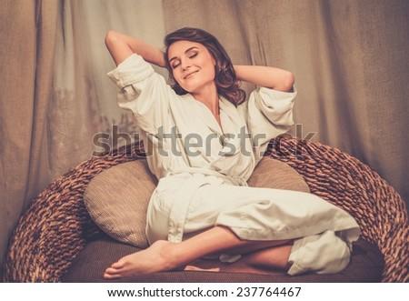 Beautiful woman relaxing in a bathrobe in spa salon