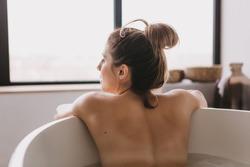 Beautiful woman relaxing in the bathtube in the bathroom.