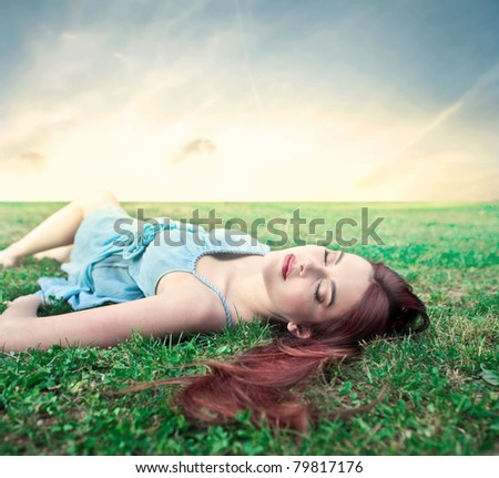 Beautiful woman relaxing on a green meadow