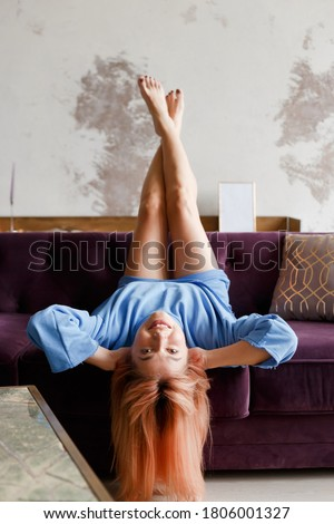 Beautiful woman relaxing on a sofa with head upside down at home Photo stock ©