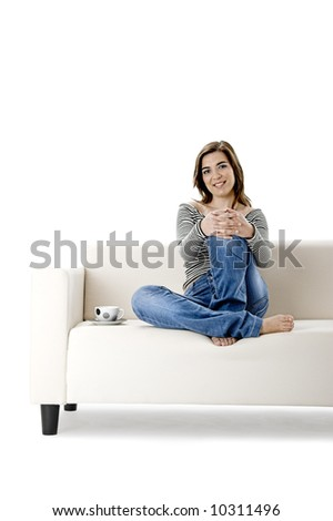 Beautiful woman relaxing on a white sofa with a cup of coffee
