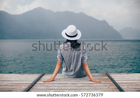 Beautiful woman relaxing on pier in Garda Lake. Vacation concept