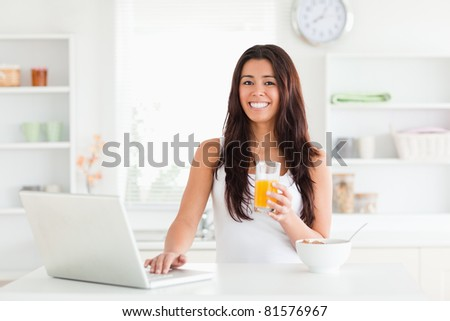 Beautiful woman relaxing with her laptop while holding a glass of orange juice in the kitchen