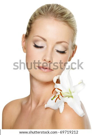 Beautiful  woman relaxing  with white lily on her body, isolated on white