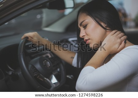 Beautiful woman rubbing her neck, feeling sore after long drive. Female driver having neck pain after whiplash injury in car crash. Woman suffering from back pain. Healthcare, safety, pain concept