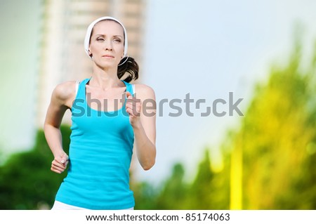 Beautiful woman running in green park on sunny summer day