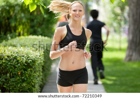 Beautiful woman running in park with people in the background