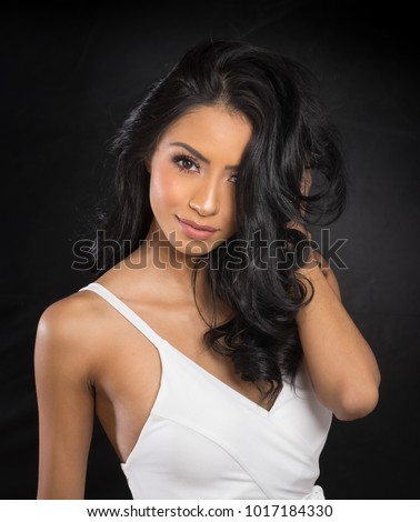 Beautiful woman's face and long dark hair wearing white dress #1017184330