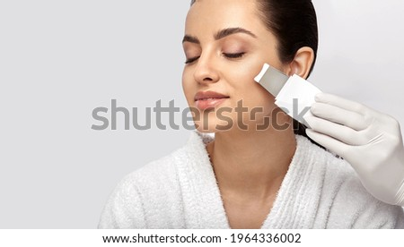 Beautiful woman's face during ultrasonic peeling skin procedure, close-up. Cleansing facial skin, remove blackheads, isolated on gray Stok fotoğraf ©