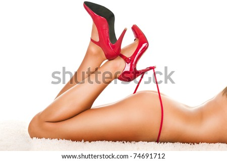 Beautiful woman's legs in heels playing with red panties - stock photo