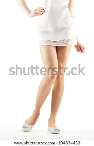 Beautiful woman's legs; legs of a girl wearing mini and flat shoes - closeup shot on white background
