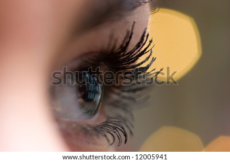 beautiful woman`s open  eye over blurred background