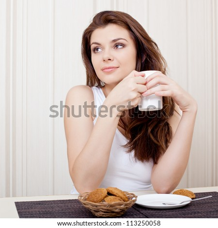 beautiful woman seated at her desk and enjoying tea and cookies