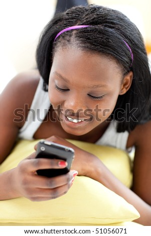 Beautiful woman sending a text lying on a sofa in the living-room