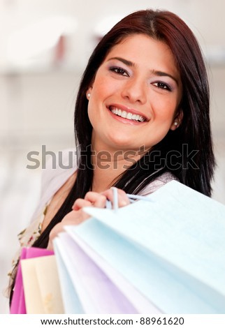 Beautiful woman shopping and holding bags looking happy