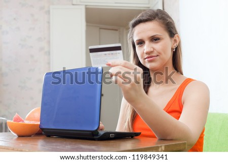 beautiful woman shopping on internet from home, using laptop and paying with credit card