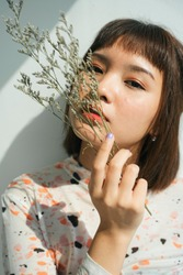 Beautiful woman short hair asian holding palea plant over white background.