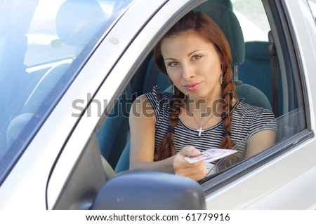 Beautiful woman show her driver's  licence in car. More images of this models you can find in my portfolio