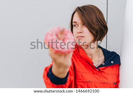 Beautiful woman showing ffinger with donut Diet diet concept. Junk food, weight loss.