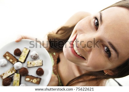 beautiful woman showing plate full of of chocolate candies in a sexy pleasant way