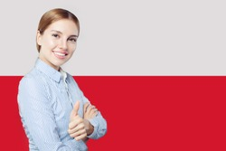 Beautiful woman showing thumb up on the Poland flag background. Travel and learn polish language concept