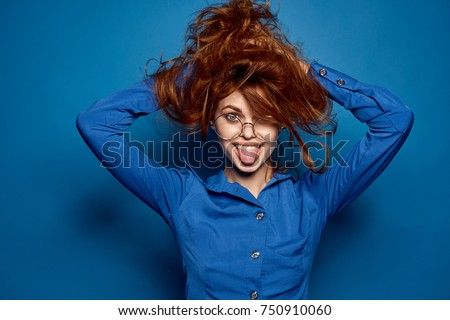 beautiful woman shows tongue holds hands with hands on blue background, crazy