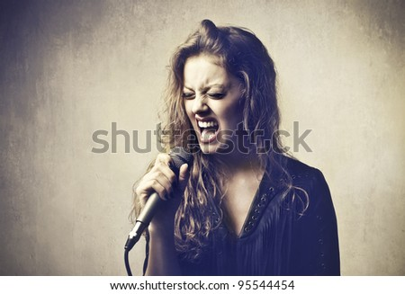 Beautiful woman singing into a microphone - stock photo