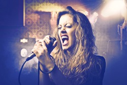 Beautiful woman singing into the microphone