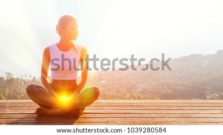 Beautiful woman sits in a pose of a half lotus on high place amazing view of the island outside, she practicing yoga meditation glowing the second sacral chakra eyes closed calm. Kundalini energy