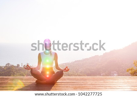Beautiful woman sits in a pose of a half lotus on high place amazing view of the island outside, she practicing yoga meditation glowing seven all chakra eyes closed calm. Kundalini energy #1042277725