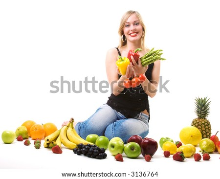Beautiful woman sitting amidst fruits holding vegetables