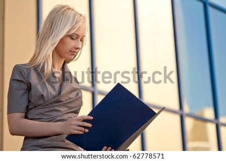 Beautiful woman sitting and reading documents outdoors