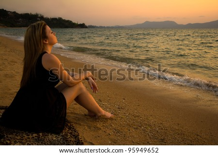 Beautiful woman sitting and relaxing on the beach at sunset