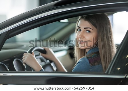 beautiful woman sitting at the wheel of a car #542597014