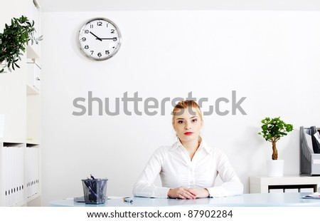Beautiful woman sitting behind the desk in her office.