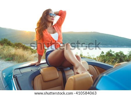 Beautiful woman sitting in cabriolet, enjoying trip on luxury modern car with open roof, fashionable lifestyle concept stock photo