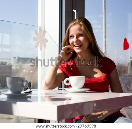 beautiful woman sitting in cafe with cup of coffee