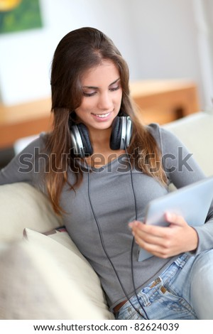 Beautiful woman sitting in sofa with touchpad
