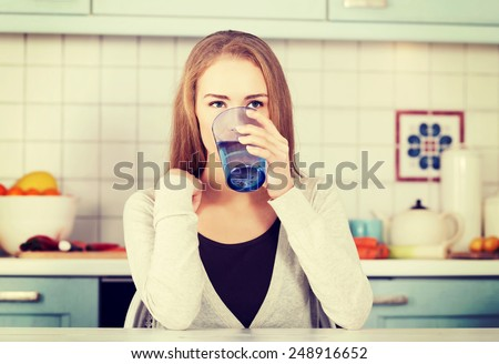 Beautiful woman sitting in the kitchen and drinking water.