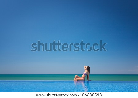 Beautiful woman sitting near infinity pool and looking to sea and horizon