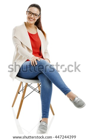 Beautiful woman sitting on a chair and smiling, isolated over white background