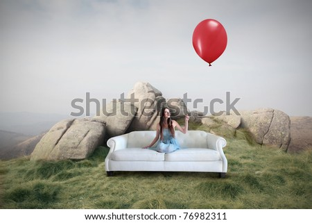 Beautiful woman sitting on a sofa on a meadow and holding a red balloon