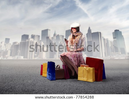 Beautiful woman sitting on a street and surrounded by shopping bags