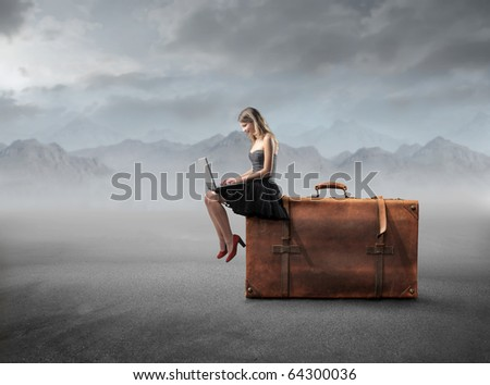 Beautiful woman sitting on a suitcase and using a laptop