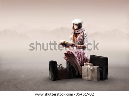 Beautiful woman sitting on a suitcase in a desert and reading a book
