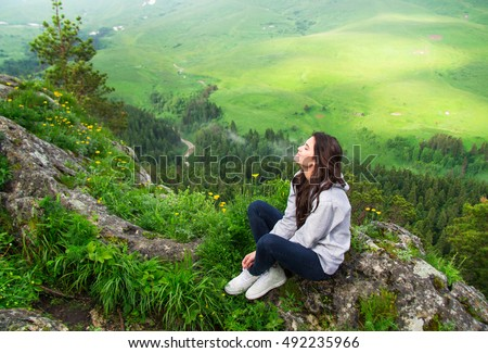 Beautiful woman sitting on mountain top and contemplating landscape